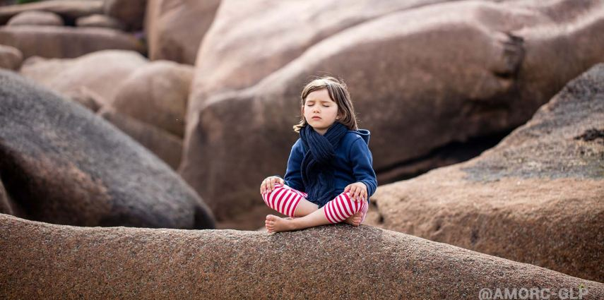 onerelaxing 5-year old child with eyes closed sitting in a granite stone landscape, meditating and breathing alone outdoor, seeking for yoga concentration, springtime